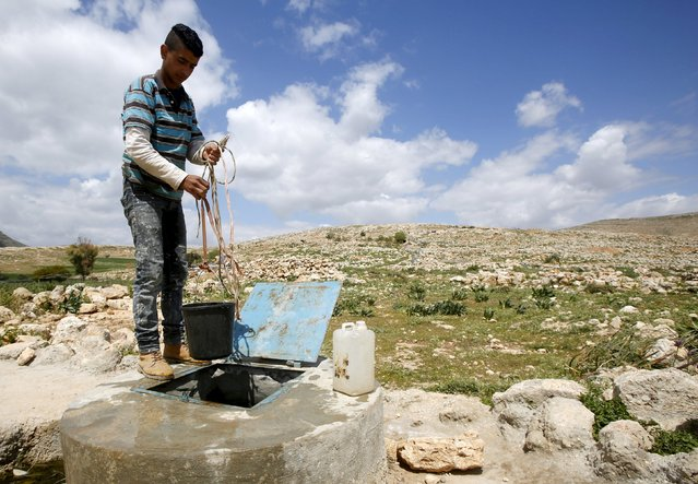 A Palestinian collects water from a well in Khirbet Tana near the West Bank city of Nablus March 29, 2016. (Photo by Abed Omar Qusini/Reuters)
