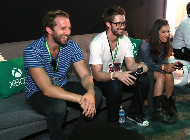 From left, Ryan Hansen, Rob Buckley and Janina Gavankar interact with newly announced games and experiences at the Xbox booth at E3 in Los Angeles on Tuesday, June 16, 2015. (Photo by Casey Rodgers/Invision for Microsoft/AP Images)