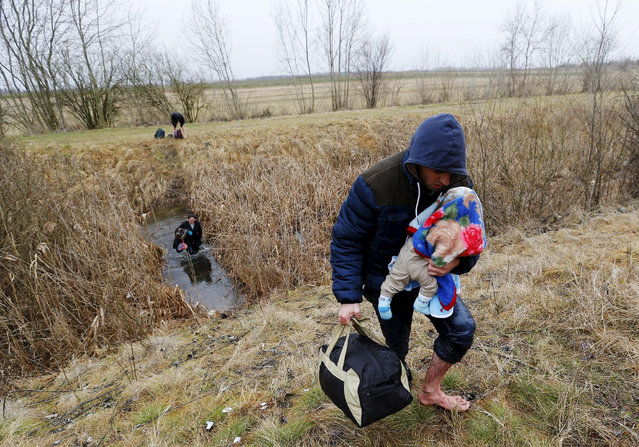 A Kosovar man wades through the water while carrying his child as they illegally cross the Hungarian-Serbian border near the village of Asotthalom, Hungary in this February 6, 2015 file photo.  Hungary announced plans on Wednesday to build a four-meter-high fence along its border with Serbia to stem the flow of illegal migrants, in a move likely to annoy human rights groups and the European Union. The landlocked central European country of 10 million people is in the EU's visa-free Schengen zone and thus an attractive destination for tens of thousands of migrants entering Europe through the Balkans from the Middle East and beyond.     REUTERS/Laszlo Balogh/Files