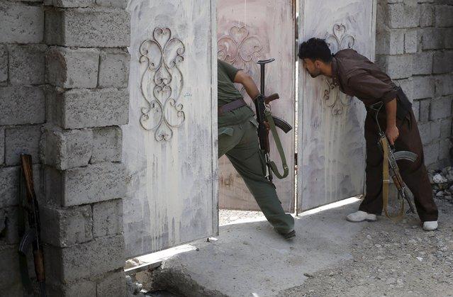 Kurdish gunmen look at a Shi'ite militiaman positions during clashes in Tuz Khurmato, Iraq, April 24, 2016. (Photo by Goran Tomasevic/Reuters)