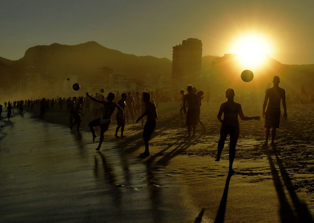 Beachgoers play with a ball at Ipanema Beach in Rio de Janeiro, Brazil, on June 29, 2019. Tourists from all over Latin America have arrived in Rio for the Copa America football tournament. (Photo by Carl de Souza/AFP Photo)