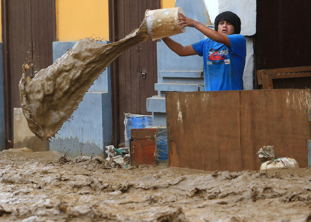 A local resident bails water from behind a barrier as a flash flood hits the city of Trujillo, 570 kilometres north of Lima on March 18, 2017, bringing mud and debris. The El Nino climate phenomenon is causing muddy rivers to overflow along the entire Peruvian coast, isolating communities and neighbourhoods. Thousands have been affected since January, and 72 people have died. Most cities face water shortages as water lines have been compromised by mud and debris. (Photo by Celso Roldan/AFP Photo)