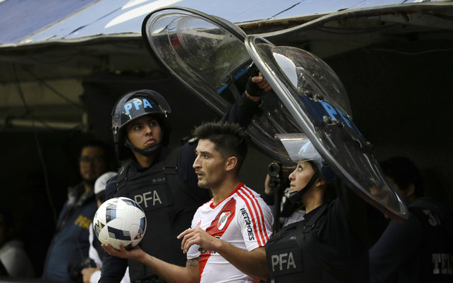 Milton Casco of River Plate is protected by police as he gets ready for a throw-in during a Argentina league soccer match against Boca Juniors in Buenos Aires, Argentina, Sunday, April 24, 2016. (Photo by Natacha Pisarenko/AP Photo)