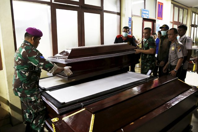 Indonesian soldiers prepare coffins outside Adam Malik hospital for victims of an Indonesian military C-130 Hercules transport plane that crashed into a residential area in the North Sumatra city of Medan, Indonesia, June 30, 2015. (Photo by Reuters/Beawiharta)