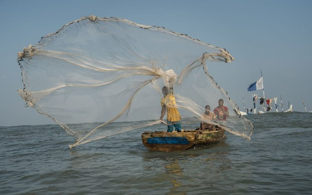 A fisherman casts his net in the waters of the Gulf of Guinea, outside Jamestown, the oldest fishing community in Accra on July 21, 2019. The fishing sector is crucially important to this West African nation. It provides support for more than two million people, up to 10 percent of the population, and the produce it generates accounts for about 60 percent of the protein in the diet of Ghanaians. But the figures are startling. United Nations data shows that production fell from almost 420,000 tonnes in 1999 to 202,000 tonnes in 2014. (Photo by Natalija Gormalova/AFP Photo)