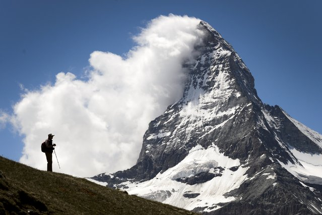 A tourists is seen in silhouette in front of the Matterhorn mountain on June 30, 2015 in Riffelalp above Zermatt. The alpine resort celebrates this year the 150 anniversary of Matterhorn's first climb. (Photo by Fabrice Coffrini/AFP Photo)