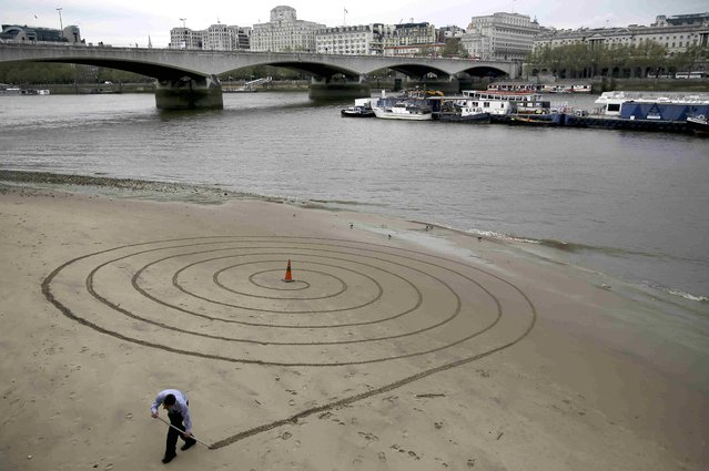 A man draws a spiral in exposed sand next to the River Thames during low tide, near the South Bank in London, Britain May 2, 2016. (Photo by Neil Hall/Reuters)