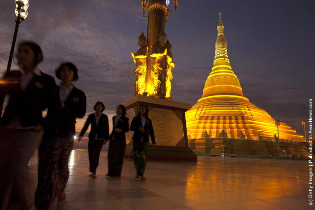 People walk by the Ouparta Thandi  pagoda which was built to mirror the famous  Shwedagon pagoda
