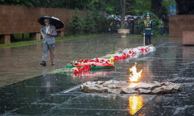 An elderly man walks past guards of honor at the World War Two memorial during Victory Day commemorations at rainy day in Almaty, Kazakhstan, May 9, 2016. (Photo by Shamil Zhumatov/Reuters)