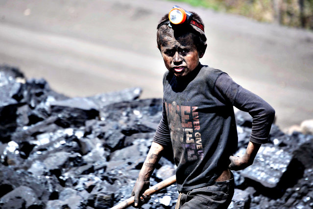 An Afghan child looks on as he works at a coal mine which collapsed on April 30 killing some 40 miners and trapping an unknown number of others in the Dar-i- Suf district of Samangan province, some 200 kms from Mazar-e-Sharif on May 1, 2014. Officials at the site in Samangan province said an explosion inside the mine on April 30 killed some 40 miners and trapped an unknown number of others. (Photo by Farshad Usyan/AFP Photo)