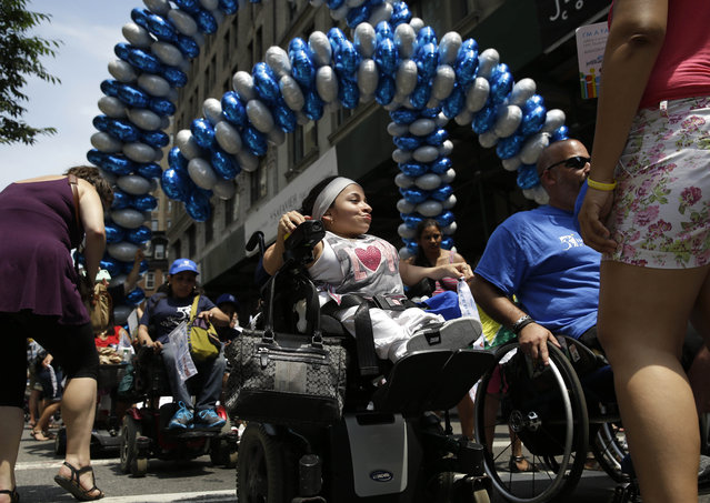Jessica Lopez, center, participates in the inaugural Disability Pride Parade, Sunday, July 12, 2015, in New York. (Photo by Seth Wenig/AP Photo)