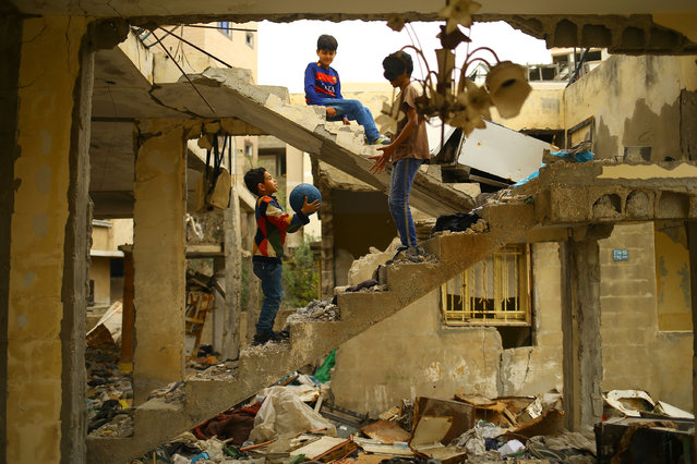 Palestinian children play amidst the ruins of a building destroyed during the 50-day war between Israel and Hamas militants during the summer of 2014 in Gaza City, on April 13, 2017. (Photo by Mohammed Abed/AFP Photo)