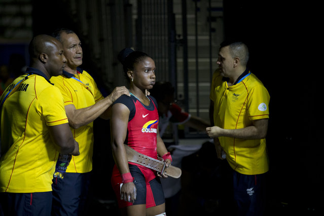 Colombia's Lina Marcela Rivas Ordonez is surrounded by coaches as she prepares for her final lift attempt in the women's 58kg weightlifting at the Pan Am Games in Oshawa, Ontario, Sunday, July 12, 2015. She won gold in the event. (Photo by Rebecca Blackwell/AP Photo)