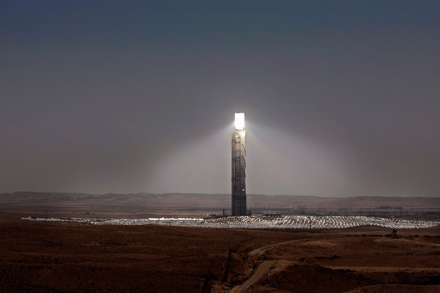 Sunlight is reflecting on the mirrors placed on the top of the Ashalim solar tower near the southern Israeli kibbutz of Ashalim in the Negev desert on April 28, 2019. In the middle of the Israeli desert, engineers built the world's highest solar tower, its peak set to resemble a giant lighthouse, beckoning toward the country's hopes in renewable energy. A field of mirrors expanding 300 hectares – the size of more than 400 football pitches – will stretch out at its base, directing sunlight toward the tower's peak to an area called the boiler, which resembles a huge lightbulb where electricity is produced. (Photo by Thomas Coex/AFP Photo)