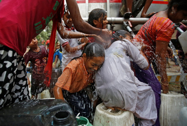Girls get drenched as they struggle to fill empty containers with water from a municipal tanker on a hot summer day in New Delhi, India, May 3, 2017. (Photo by Adnan Abidi/Reuters)