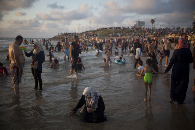 Muslims, many of whom are Palestinians from the West Bank, bathe in the Mediterranean Sea during the last day of the Eid al-Fitr holiday as the sun sets in Tel Aviv, Israel, Sunday, July 19, 2015. The three-day Eid al-Fitr holiday marks the end of the holy fasting month of Ramadan. One of the most important holidays in the Muslim world, Eid al-Fitr, is marked with prayers, family reunions and other festivities. (Photo by Ariel Schalit/AP Photo)