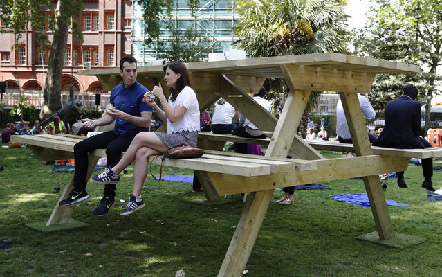People sit at an oversize picnic table in Soho Square in London May 19, 2014. (Photo by Luke MacGregor/Reuters)