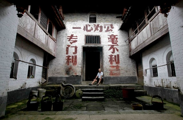 """A villager sits in a doorway of a house where revolutionary slogans are painted on the wall in Dongzhai village, Guangxi Zhuang Autonomous Region, China, July 19, 2015. The slogan on the wall reads: """"Just for the people (L), wholeheartedly for the public (top) and never for the self"""". (Photo by Reuters/Stringer)"""