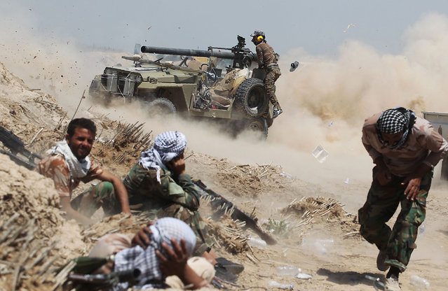 Iraqi pro-government forces fire an anti-tank cannon near al-Sejar village, north-east of Fallujah, on May 25, 2016, as they take part in a major assault to retake the city from the Islamic State (IS) group. Iraqi forces, consisting of special forces, soldiers, police, paramilitary-fighters and pro-government tribesmen, launched a major assault to retake Fallujah, the scene of deadly battles during the US occupation and one of the toughest targets yet in Baghdad's war on the Islamic State group. (Photo by Ahmad Al-Rubaye/AFP Photo)
