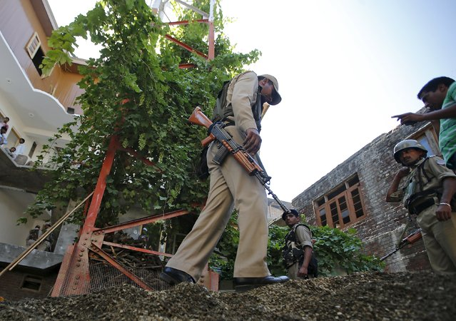 Indian Central Reserve Police Force (CRPF) personnel inspect the site of a grenade attack next to a telecom tower in Srinagar, July 24, 2015. On Friday, three attacks were carried out on telecoms facilities in the Muslim-majority state's summer capital of Srinagar, one of them near the office of Chief Minister Mufti Mohammad Sayeed. (Photo by Danish Ismail/Reuters)