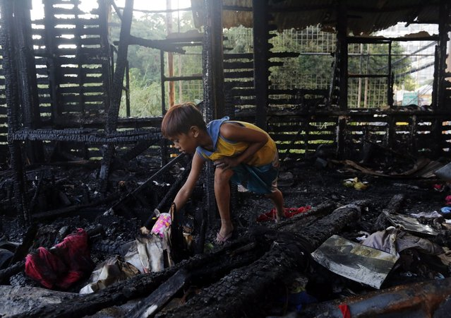 A Filipino boy searches for salvageable materials on a burnt house following a fire in Manila, Philippines, 06 June 2016. According to Bureau of Fire Protection (BFP) arson investigator John Joseph Jalique, the fire took place at a residential area near a mosque, the night before the start of the holy fasting month of Ramadan, destroying 100 houses and around 200 families were affected. (Photo by Francis R. Malasig/EPA)