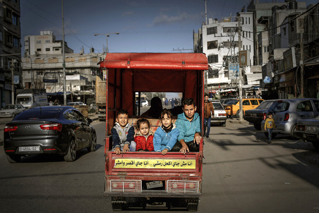 Palestinian children ride in the back of a tuktuk with their father on their way to a street market in Gaza City on December 6, 2019. (Photo by Mohammed Abed/AFP Photo)