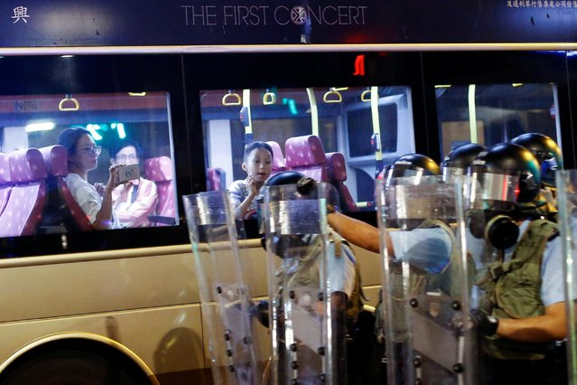 People watch from a bus as police faces anti-extradition bill protesters during clashes in Sham Shui Po in Hong Kong, August 14, 2019. (Photo by Thomas Peter/Reuters)