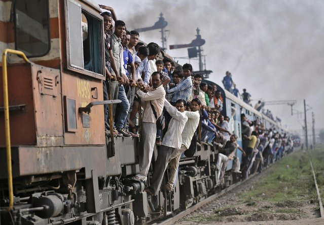 Passengers travel on an overcrowded train at Loni town in the northern Indian state of Uttar Pradesh July 8, 2014. India plans to spend 654.5 billion rupees ($10.95 billion) on its railways in 2014/2015, the government said in its railway budget on Tuesday. (Photo by Anindito Mukherjee/Reuters)
