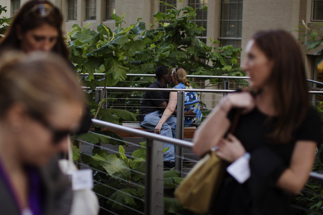 A couple kisses while pedestrians walk past on the High Line park in New York, June 12, 2013. (Photo by Lucas Jackson/Reuters)