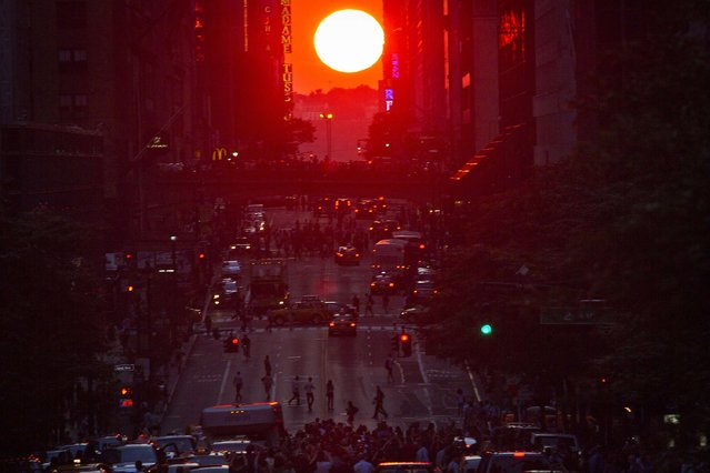 "People crowd onto 42nd Street as they take photos of the ""Manhattanhenge"" phenomenon in the Manhattan borough of New York July 11, 2014. Manhattanhenge, coined by astrophysicist Neil deGrasse Tyson, occurs twice a year, when the setting sun aligns itself with the east-west grid of streets in Manhattan. (Photo by Carlo Allegri/Reuters)"