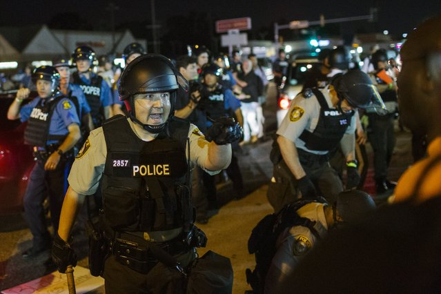 St Louis County police officers interact with anti-police demonstrators during protests in Ferguson, Missouri August 10, 2015. (Photo by Lucas Jackson/Reuters)