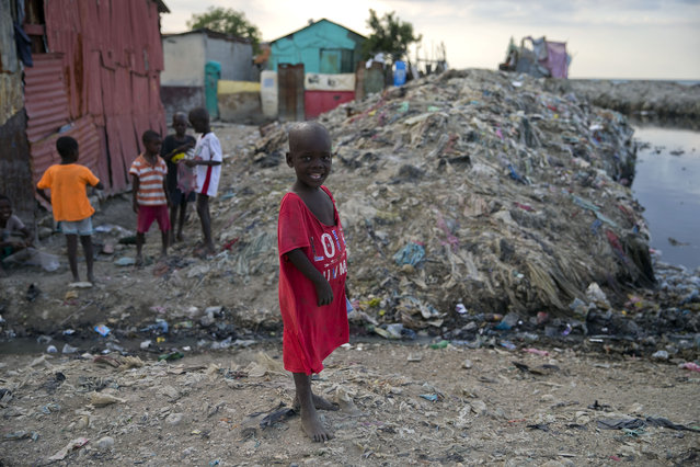 In this December 3, 2019 photo, a boy stands near an open sewage canal in Cite Soleil slum of Port-au-Prince, Haiti. The boys was flying a kite along with his friends. The United Nations recently said 3.7 million people are facing emergency levels of food insecurity, including 1 million who are at stage four, one level below famine. (Photo by Dieu Nalio Chery/AP Photo)