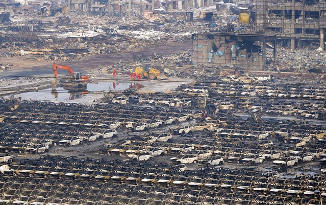 Rescuers walk next to damaged vehicles at the site of Wednesday night's explosions in Binhai new district of Tianjin, China, August 15, 2015. (Photo by Reuters/Stringer)