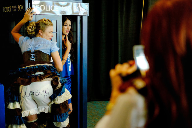 "Danica Lisiewicz, of Los Angeles, CA, left, dressed as a ""can-can version of the 10th Doctor Who"", as she described her handmade costume, poses for photos with Allie Marie, of Irvine, CA, in her homemade life-size Tardis during the 45th annual San Diego Comic-Con on July 24, 2014 in San Diego, California. (Photo by T. J. Kirkpatrick/Getty Images)"