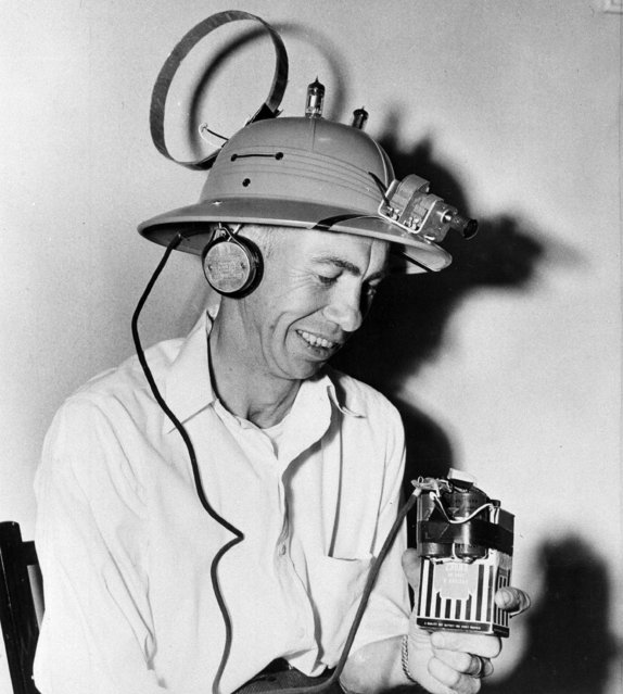 """Frank W. Elmore, an electrician, wears a hat radio on his head in Spokane, Wash., May 24, 1952. The dial is in the front as tubes that look like horns stick up on top. The circular object in the back is the aerial antenna. A pocket battery, earphones and some other equipment inside the helmet do the rest. """"It's just the thing for a gardener"""", says Elmore. His hat can tune in all the local stations. (Photo by AP Photo)"""