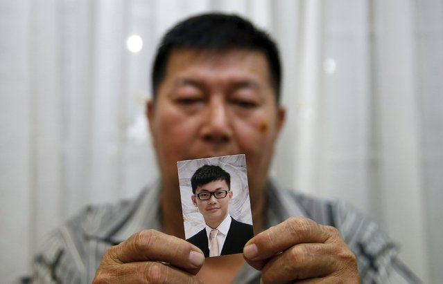 Neon Hock Guan, injured in Monday's blast in Bangkok, holds up a picture of his son Neoh Jai Jun who was killed in the attack, at his home in Butterworth, Malaysia, August 19, 2015. Thai police said on Wednesday that a suspect captured by CCTV cameras minutes before a bomb exploded at Bangkok's Erawan shrine was a foreigner, and his appearance suggested he might be from Europe or the Middle East. (Photo by Olivia Harris/Reuters)