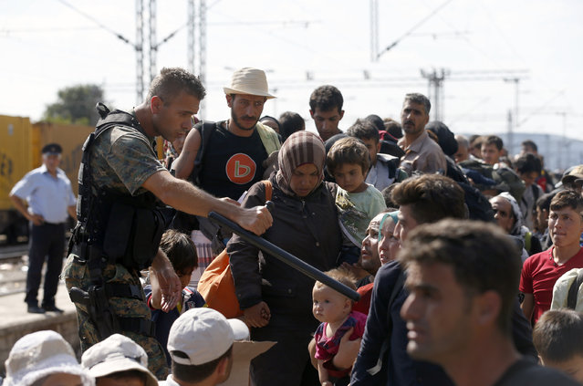 A police officer gives instructions to migrants rushing to board a train that would take them towards Serbia, at the railway station in the southern Macedonian town of Gevgelija, Wednesday, August 20, 2015. (Photo by Darko Vojinovic/AP Photo)