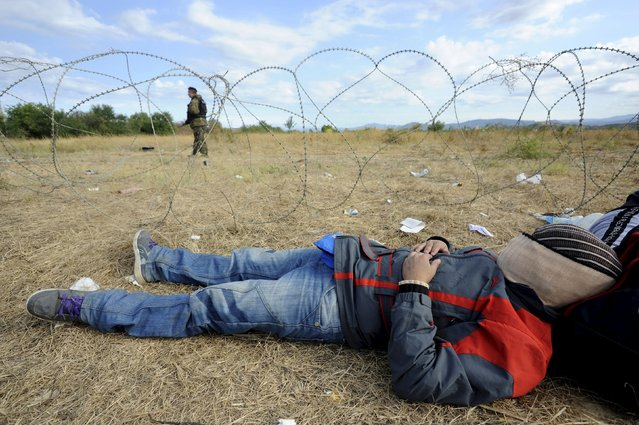 A migrant rests as a Macedonian policeman stands guard at the Greek-Macedonian border, August 21, 2015. (Photo by Alexandros Avramidis/Reuters)