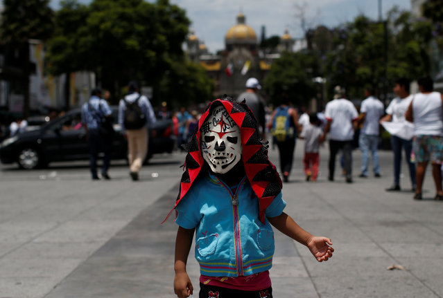 A child wears a wrestler's mask during the annual lucha libre pilgrimage to the Basilica of Our Lady Guadalupe in Mexico City, Mexico on August 18, 2017. (Photo by Carlos Jasso/Reuters)