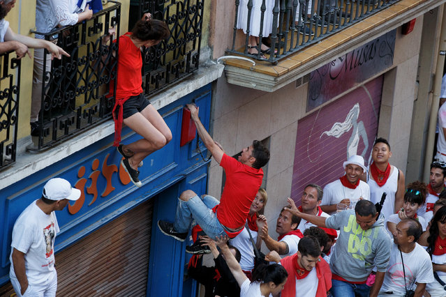 A reveller climbs on to a balcony before the start of Fuente Ymbro's fighting bulls running during the second day of the San Fermin Running of the Bulls festival on July 7, 2016 in Pamplona, Spain. (Photo by Pablo Blazquez Dominguez/Getty Images)