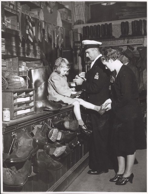Woman and child buying shoes in the shoe section of Bell and Macaulay's Store, Drouin, Victoria, ca. 1944