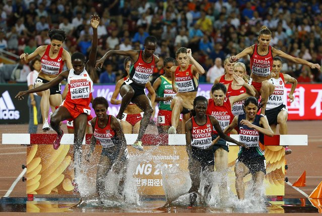 Athletes clear a water obstacle during the women's 3000 metres steeplechase final at the IAAF World Championships at the National Stadium in Beijing, China August 26, 2015. (Photo by Damir Sagolj/Reuters)
