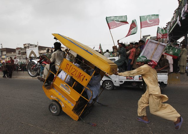 A supporter (R) of cricketer-turned-opposition politician Imran Khan runs to catch an overladen rickshaw, which had its front off the ground, to join others in the Freedom March in Gujrat August 15, 2014. Thousands of protesters began to march on the Pakistani capital from the eastern city of Lahore on Thursday, buoyed by a last-minute court order that a peaceful march could go ahead and a government promise to obey the ruling. (Photo by Akhtar Soomro/Reuters)