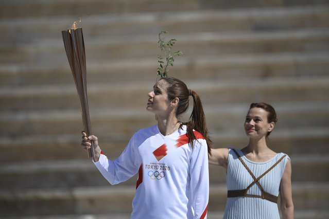 Katerina Stefanidi, Greek Olympic Champion in pole vault, holds the Olympic torch during the Olympic flame handover ceremony for the 2020 Tokyo Summer Olympics, in Athens, Thursday, March 19, 2020. The ceremony was held behind closed doors and with the presence of few members of the media because of fears over the new coronavirus. (Photo by Aris Messinis/Pool via AP Photo)