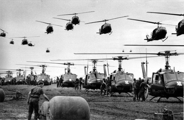 U.S. Army helicopters providing support for U.S. ground troops  fly into a staging area fifty miles northeast of Saigon, Vietnam, August 28, 1966. Helicopter fuel is stored in the large rubber tanks, foreground. (Photo by Henri Huet/AP Photo)