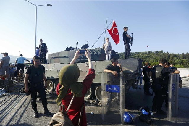 A woman takes a photo of policemen after troops involved in the coup surrendered on the Bosphorus Bridge in Istanbul, Turkey July 16, 2016. (Photo by Murad Sezer/Reuters)