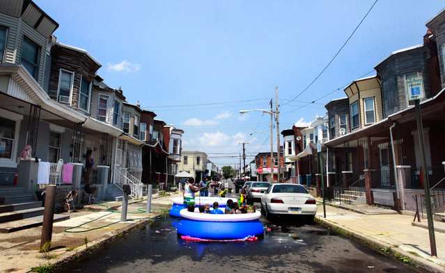 Residents block cars and set up a pool on the street on June 20, 2012, in Philadelphia. Temperatures climbed toward the high 90s along the Eastern Seaboard as an unusually early hot spell heralded the official start of summer. (Photo by Brynn Anderson/AP Photo)