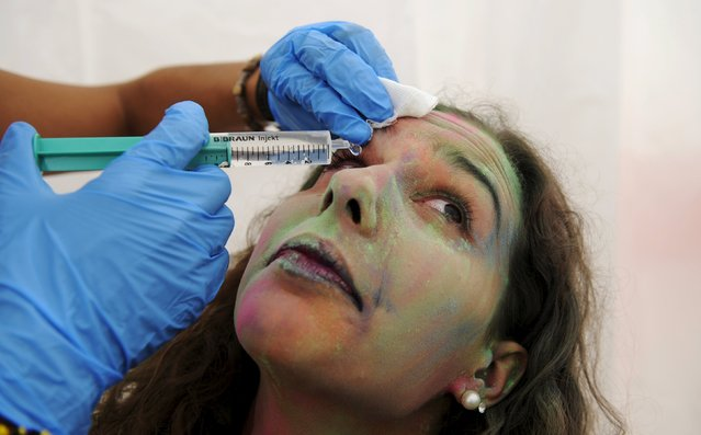 A member of Red Cross cleans the eye of a reveller during the Holi Party Festival at the Niemeyer Center in Aviles, northern Spain, August 29, 2015. (Photo by Eloy Alonso/Reuters)