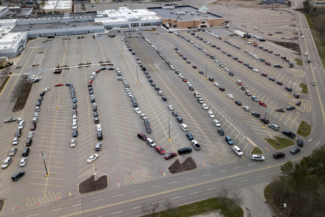 Cars line up in the parking lot at a drive-thru food pantry at Woodland Mall in Grand Rapids, Thursday April 1, 2020. The National Guard helped distribute the food at the site which was run by Feeding America West Michigan. The pantry is one of many set up after the new coronavirus COVID-19 arrived in Michigan. (Photo by Neil Blake/The Grand Rapids Press via AP Photo)