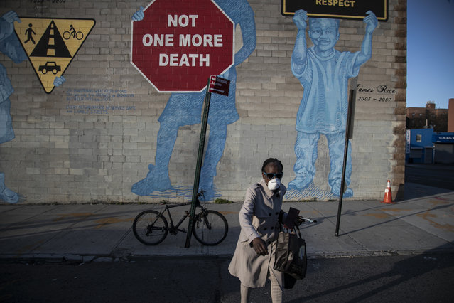 """A woman wearing a mask crosses the street in front of a mural about traffic accidents reading, """"NOT ONE MORE DEATH"""" in the Brooklyn borough of New York, March 27, 2020. (Photo by Wong Maye-E/AP Photo)"""